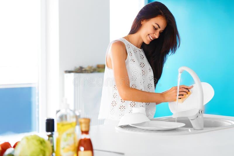 Mulher que lava os pratos na cozinha fotos de stock