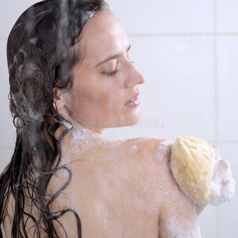 Mulher que lava seu gel do chuveiro do corpo foto de stock royalty free