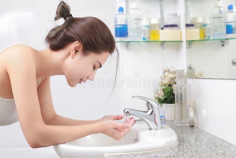 Mulher que lava sua cara com água acima do dissipador do banheiro fotos de stock royalty free