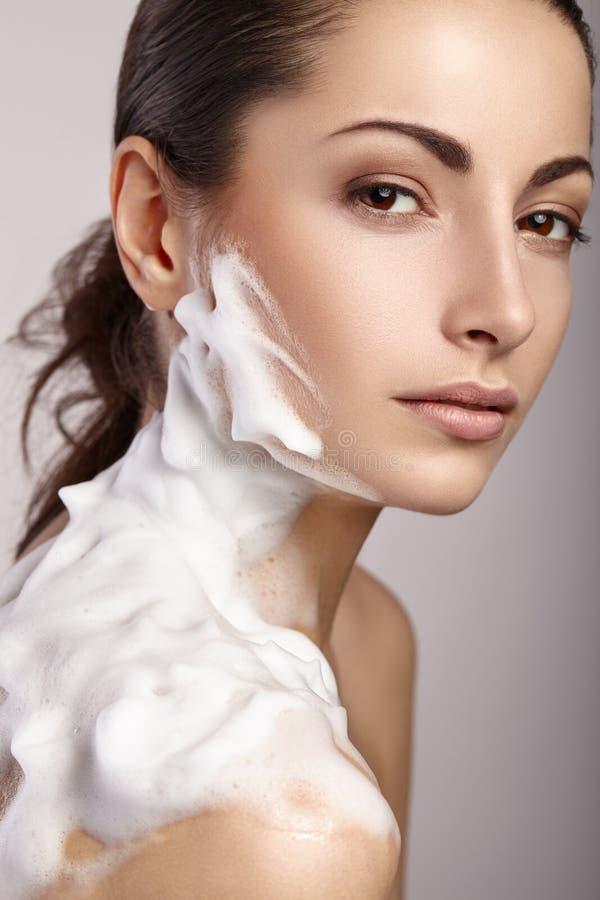 Mulher que lava sua face com espuma de limpeza imagem de stock