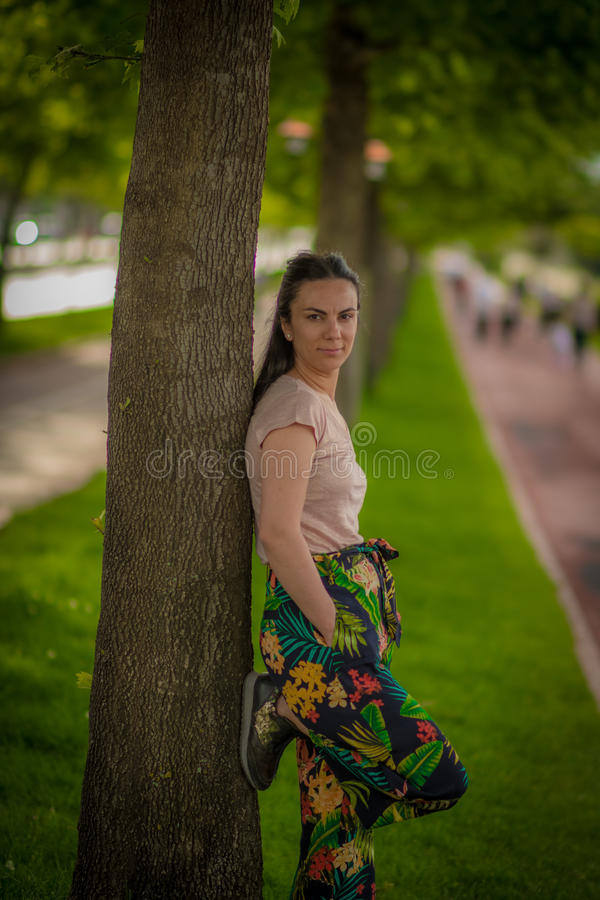 Mulher que leanning na árvore imagens de stock
