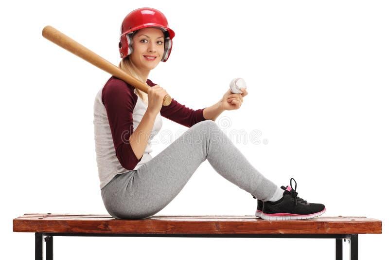 Mulher que levanta com basebol e bastão no banco de madeira imagem de stock royalty free