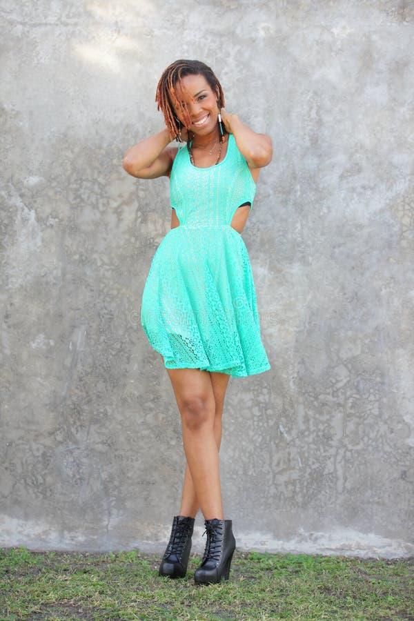 A mulher que levanta em uma cerceta à moda coloriu o vestido foto de stock