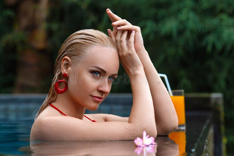 Mulher que levanta na piscina tropical imagens de stock royalty free