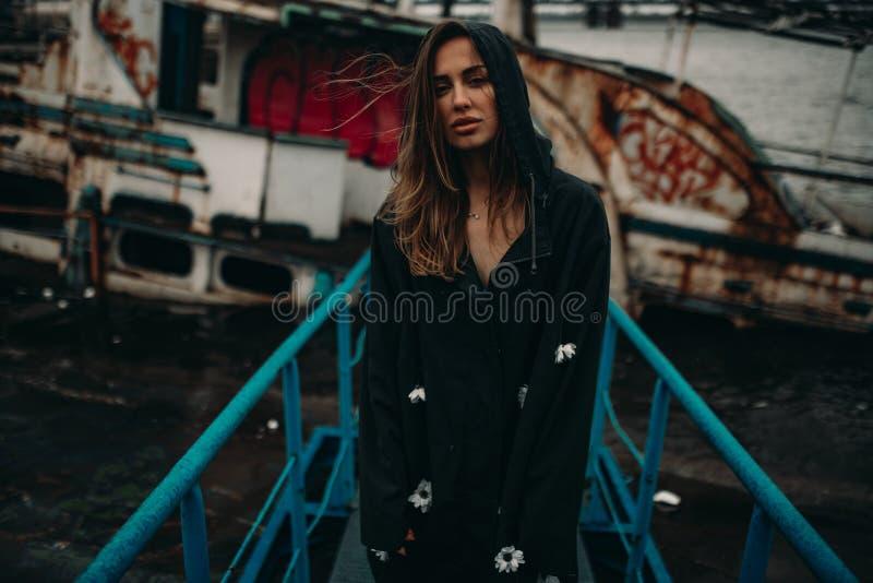 Mulher que levanta na ponte na perspectiva de um navio oxidado velho fotografia de stock royalty free