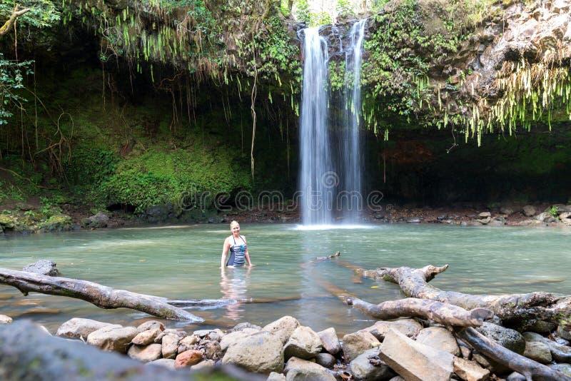 Mulher que levanta para a foto cachoeira em Maui, Havaí - Twin Falls no movimento, parada do turista na estrada a Hana fotos de stock royalty free