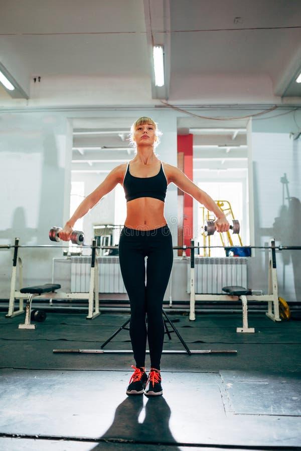 Mulher que levanta pesos no gym imagem de stock