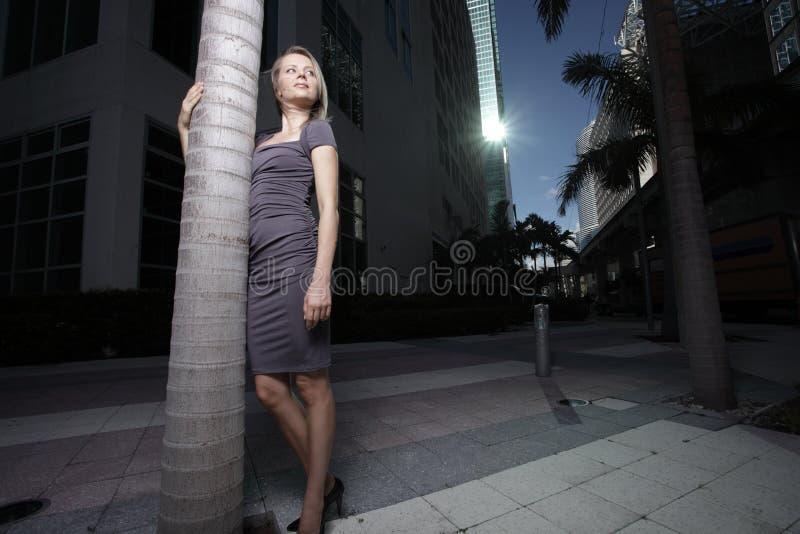 Mulher que levanta por uma árvore na cidade imagens de stock
