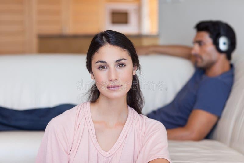 Mulher que levanta quando seu noivo escutar a música foto de stock