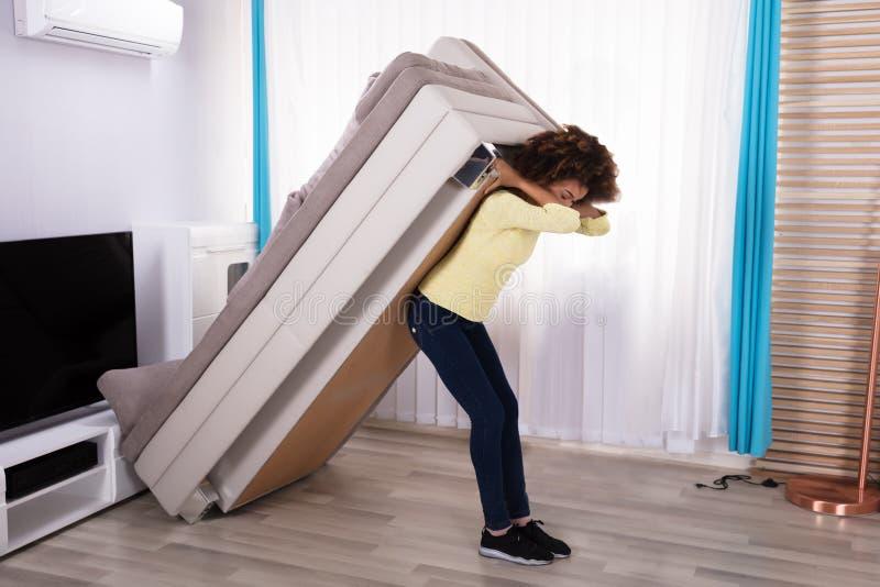 Mulher que levanta Sofa In Living Room imagens de stock