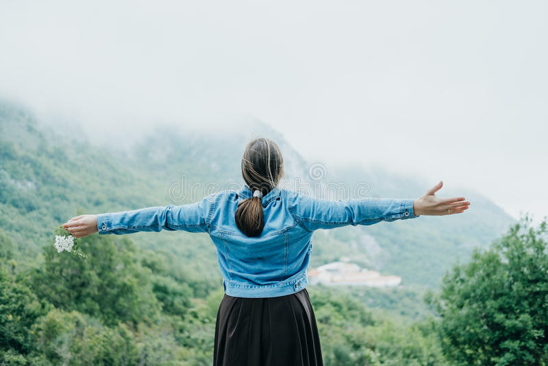 Mulher que levanta suas mãos acima na perspectiva de uma montanha, fotos de stock