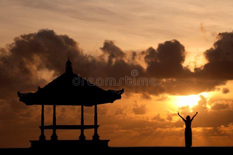 Mulher que levanta suas mãos no nascer do sol imagem de stock