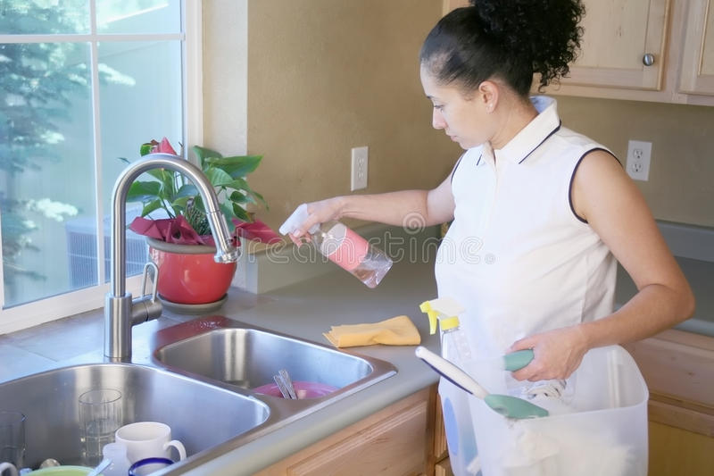 Mulher que limpa a cozinha fotografia de stock
