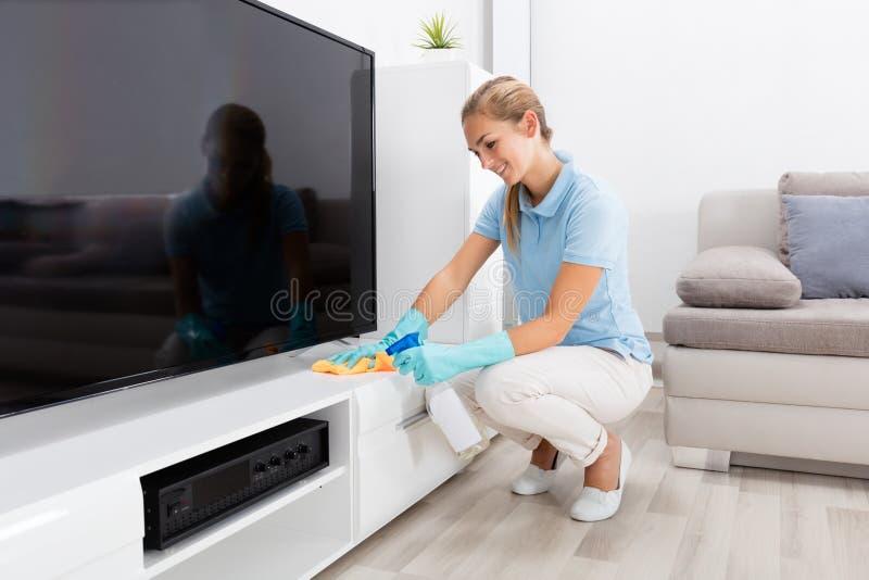 Mulher que limpa a mobília da sala de visitas fotografia de stock