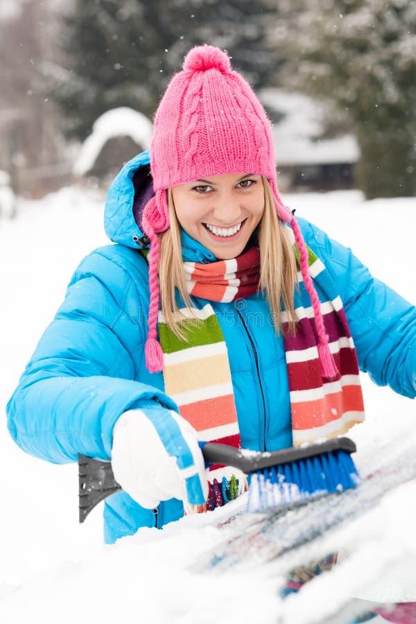 Mulher que limpa o pára-brisa do carro usando a neve da escova fotografia de stock