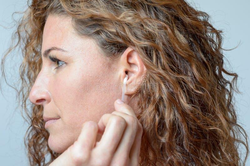 Mulher que limpa sua orelha com um cotonete de algodão imagens de stock royalty free