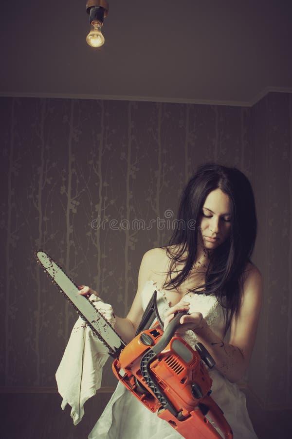 Mulher que limpa sua serra de cadeia fotografia de stock royalty free