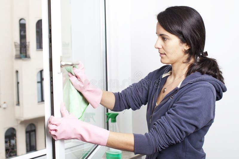Mulher que limpa um indicador fotografia de stock