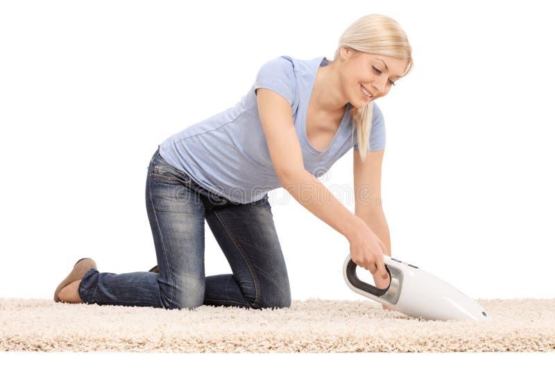 Mulher que limpa um tapete com o aspirador de p30 handheld foto de stock
