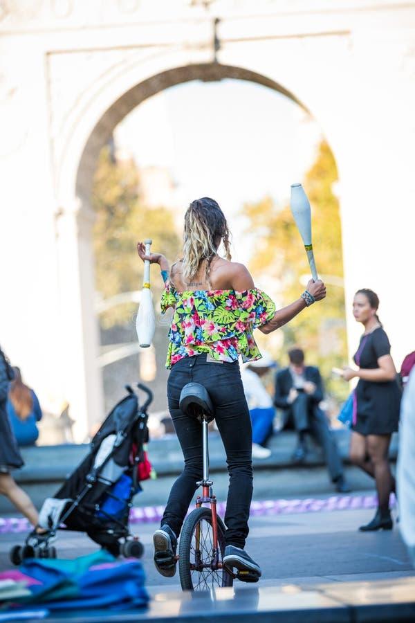 Mulher que manipula com pinos ao montar o Unicycle, no o médio imagem de stock