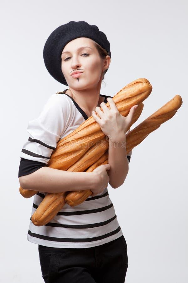 Mulher que mantém baguettes isolados no branco foto de stock