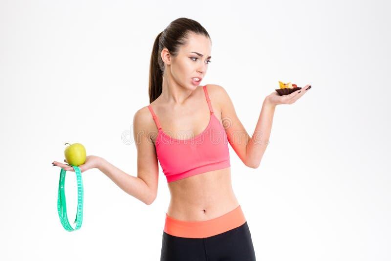 Mulher que mantém a maçã, a fita mesuring e o bolo fazendo uma escolha fotografia de stock royalty free