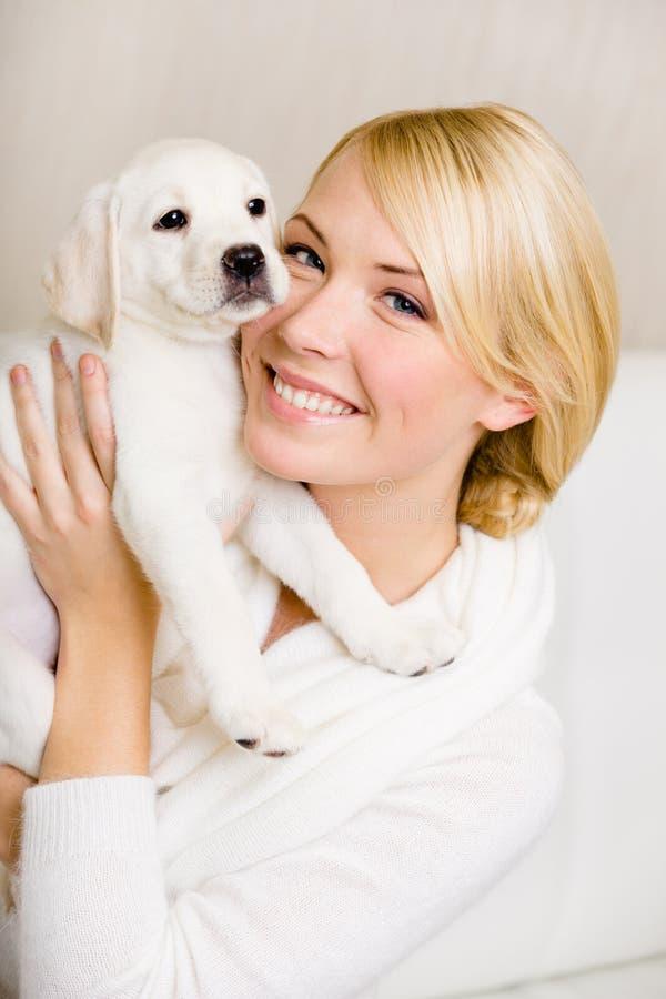 Mulher que mantém o cachorrinho branco perto de sua cara imagens de stock royalty free