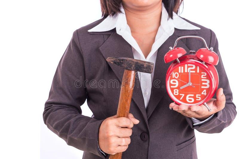Mulher que mantém o martelo e o despertador vermelho isolados no branco Brea foto de stock royalty free