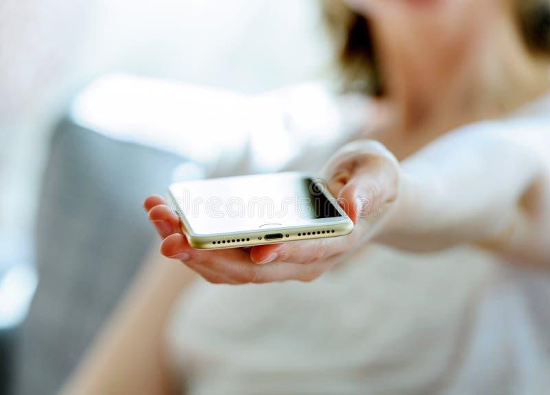 Mulher que mantém o porto novo da iluminação do iphone novo 7 positivo imagens de stock