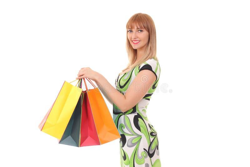 Mulher que mantém sacos de compras contra o fundo branco foto de stock