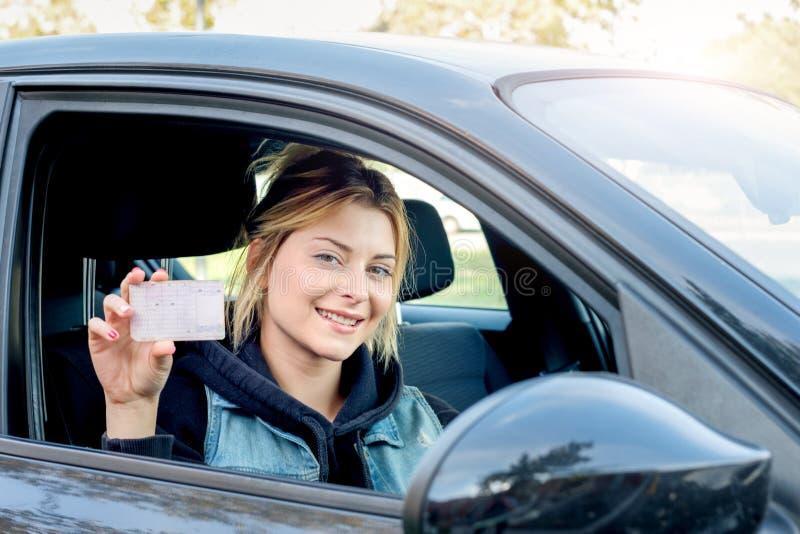 Mulher que mantém sua carteira de motorista nova assentada no carro imagens de stock royalty free