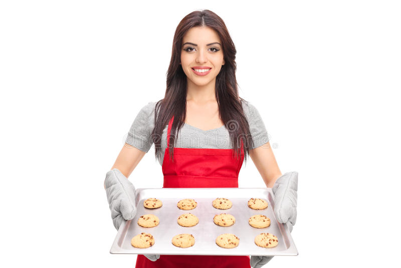 Mulher que mantém uma bandeja completa de cookies dos pedaços de chocolate fotografia de stock royalty free