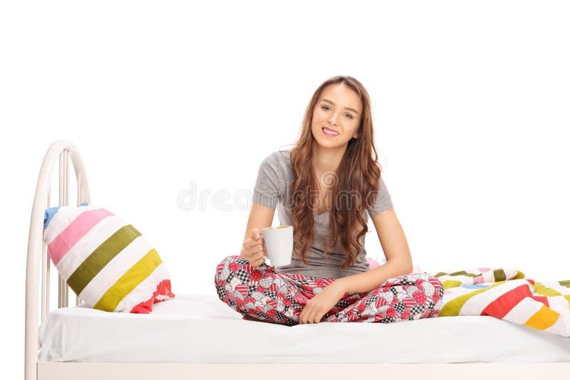 Mulher que mantém uma xícara de café assentada na cama fotografia de stock