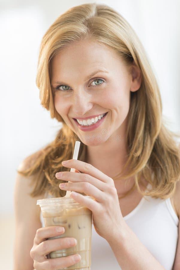 Mulher que mantem o milk shake do chocolate de vidro fotografia de stock royalty free