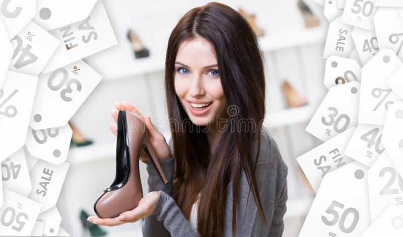 Mulher que mantem a sapata café-colorida Venda do Natal foto de stock