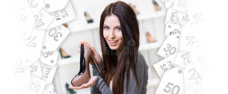 Mulher que mantem a sapata café-colorida Venda preta de sexta-feira imagem de stock