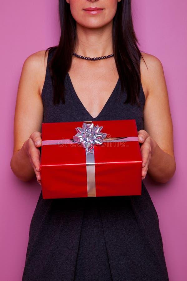 Mulher que mantem um presente envolvido no papel vermelho imagem de stock