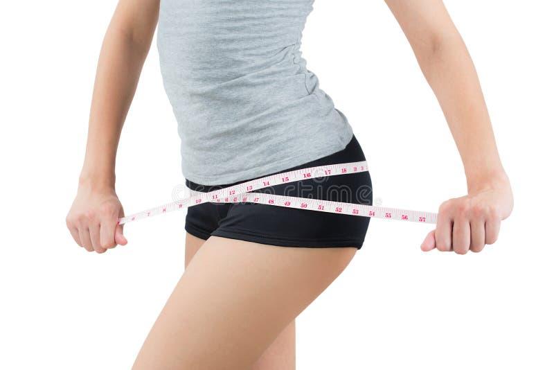 A mulher que mede seu quadril perde o peso e o conceito de corpo saudável o imagens de stock