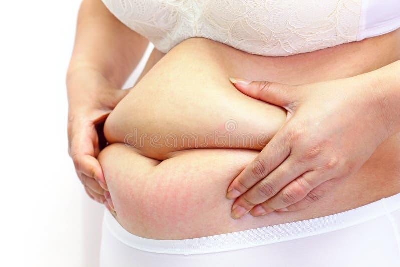 Mulher que mede sua gordura da barriga com suas mãos imagens de stock