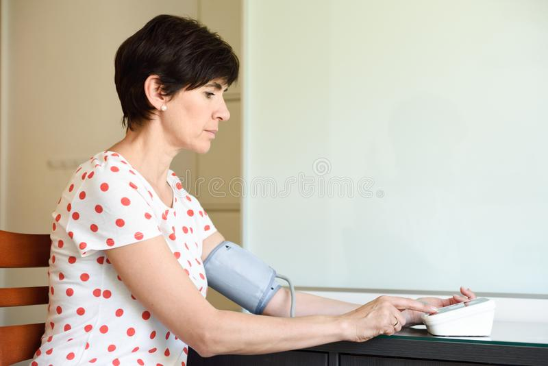Mulher que mede sua própria pressão sanguínea em casa fotografia de stock