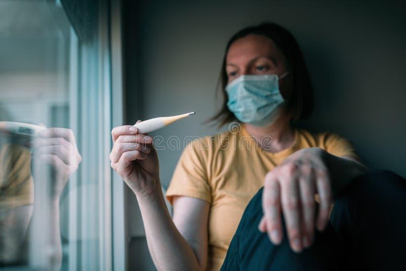 Mulher que mede a temperatura corporal de autoisolamento termômetro digital eletrônico fotografia de stock