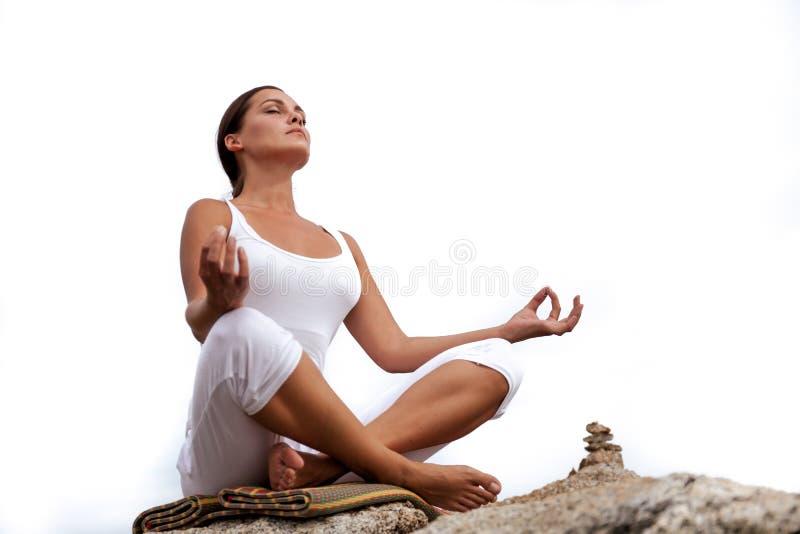 Mulher que medita em uma pose da ioga na praia imagens de stock