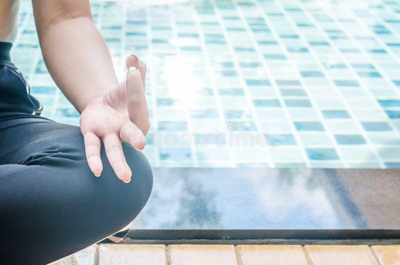 Mulher que medita em uma posição da ioga dos lótus na piscina azul imagem de stock