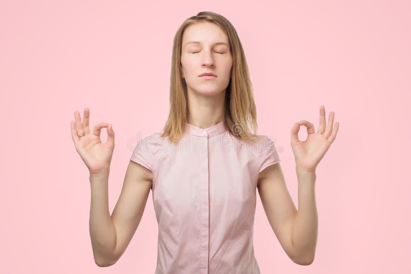 Mulher que medita, guardando suas mãos no gesto da ioga, sentindo calmo e positivo fotografia de stock
