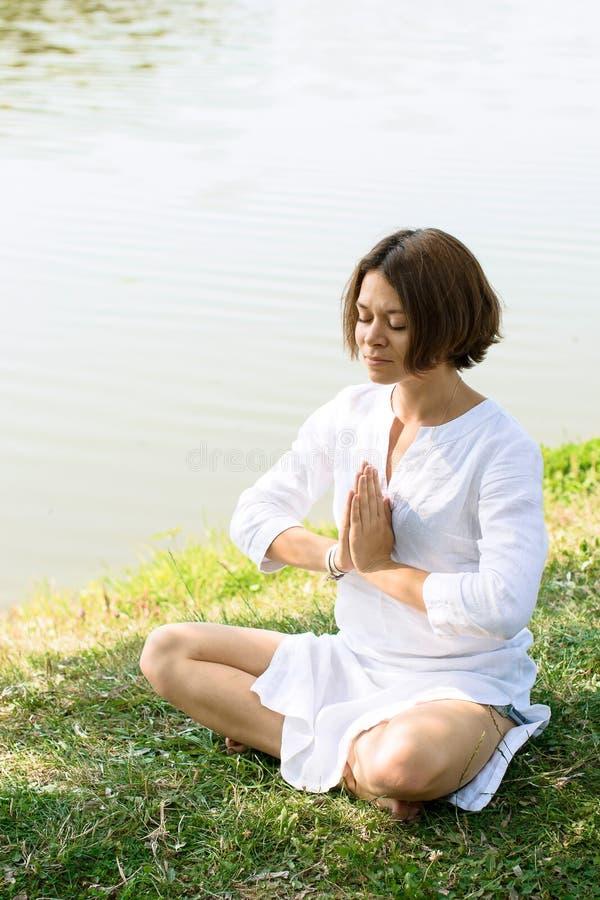 Mulher que medita na pose fácil na grama no rio-banco imagens de stock royalty free