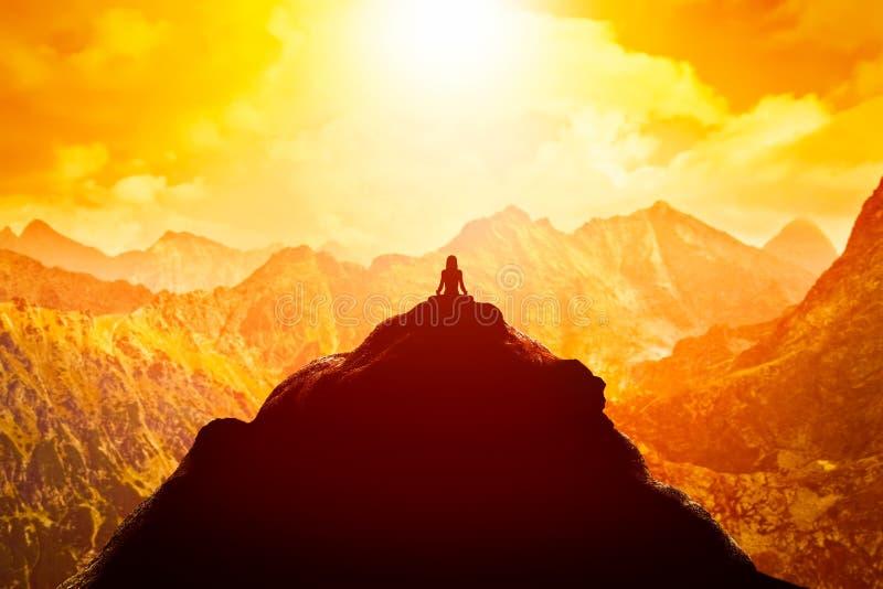 Mulher que medita na posição de assento da ioga sobre a parte superior do montanhas acima das nuvens no por do sol ilustração stock