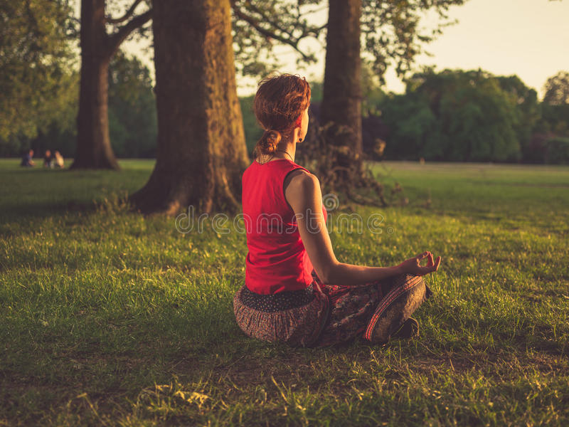 Mulher que medita no parque no por do sol imagem de stock