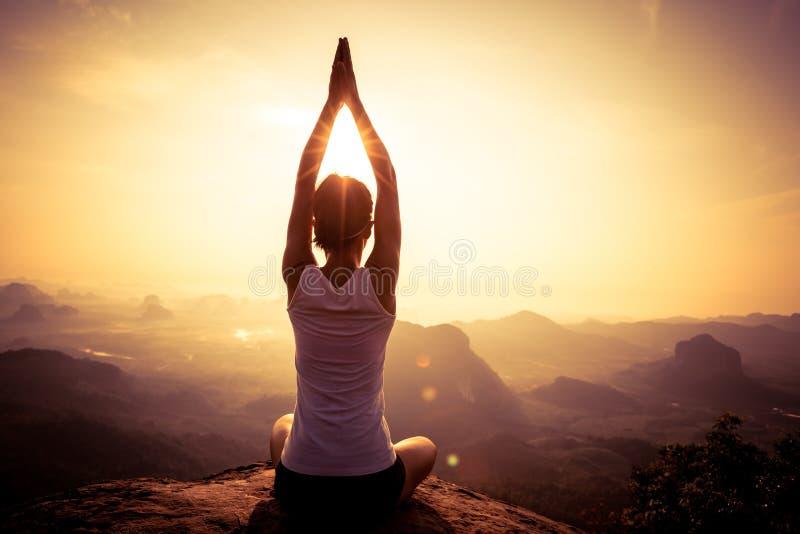 Mulher que medita sobre o pico de montanha do nascer do sol fotos de stock