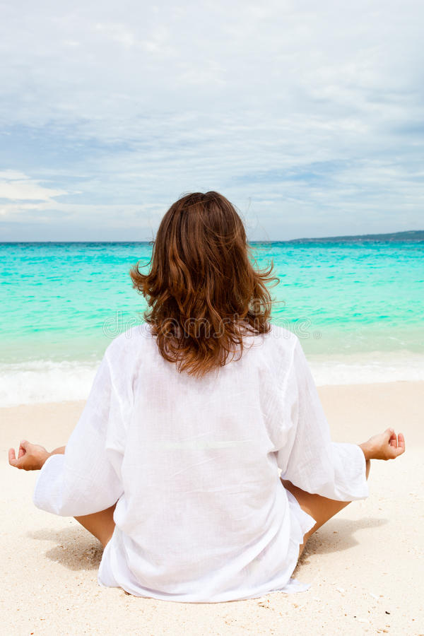 Mulher que medita sobre a praia fotos de stock
