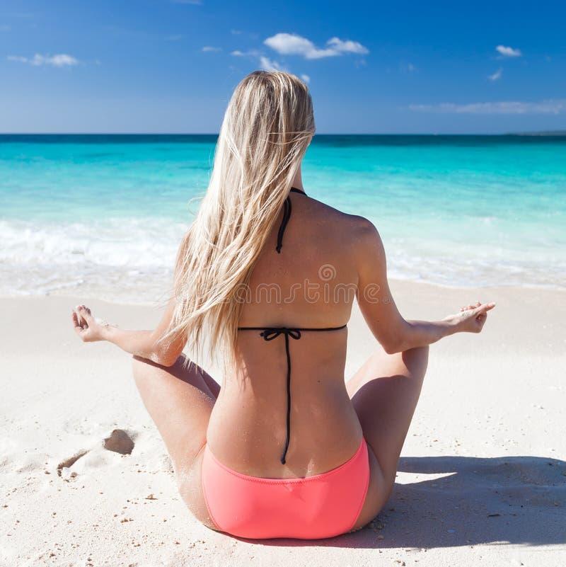 Mulher que medita sobre a praia na posição de lótus imagens de stock